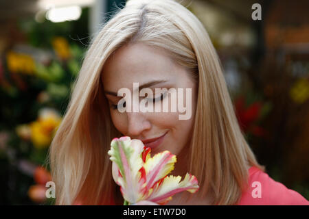 Blond woman smelling flower on weekly market - Stock Photo