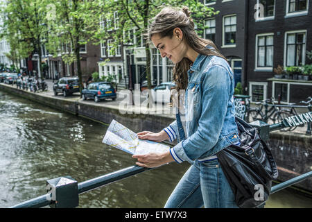 Netherlands, Amsterdam, female tourist looking at city map in front of town canal - Stock Photo
