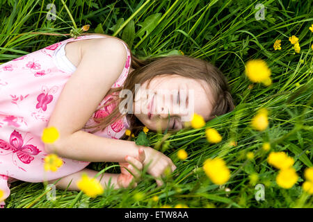 Smiling little girl with closed eyes lying on a flower meadow - Stock Photo