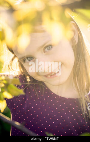 Portrait of smiling little girl looking through twigs of a tree - Stock Photo