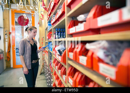 Young woman in storeroom of a bicycle repair shop - Stock Photo