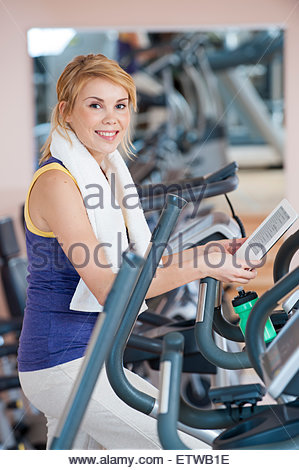Portrait of smiling young woman with e-book in a gym - Stock Photo