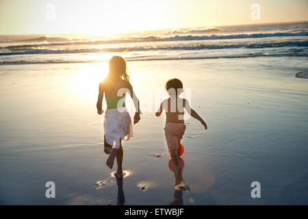 Boy and girl running on beach at sunset - Stock Photo