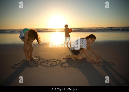 Children on the beach at sunset drawing in sand - Stock Photo