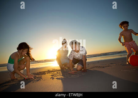 Family on the beach at sunset drawing in sand - Stock Photo