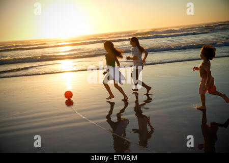 Three children playing with ball on the beach at sunset - Stock Photo