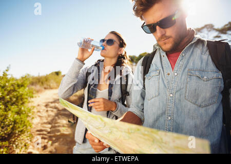 Couple on country walk together, summer vacation in countryside. Young man reading a map while woman drinking water - Stock Photo