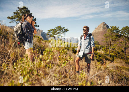 Young woman taking picture of boyfriend in countryside while trekking during summer vacation. Young couple hiking. - Stock Photo