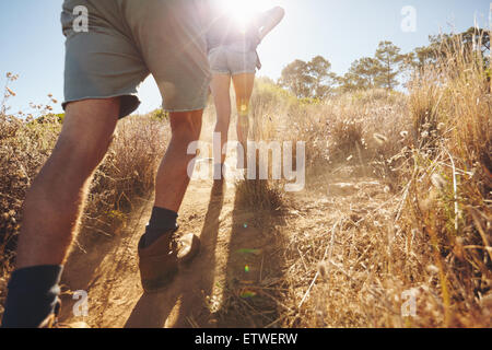 Rear view of two people going uphill on a mountain trail on hot summer day. Couple on hiking trip. Low section image - Stock Photo