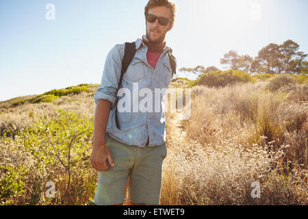 Portrait of handsome young man hiking in nature. Caucasian man walking on country trail on hot sunny day. - Stock Photo