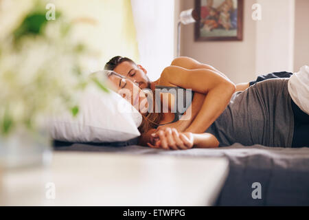 Image of young couple sleeping soundly in bed together. Husband and wife sleeping together in their bedroom. - Stock Photo