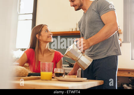 Shot of young couple having breakfast in kitchen. Young man standing and serving coffee with woman sitting by breakfast - Stock Photo