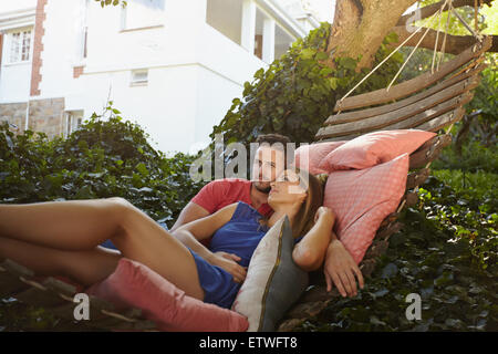 Young couple relaxing on a garden hammock. They are looking away in thought. Relaxed man and woman swinging on a - Stock Photo