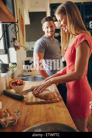 Caucasian couple together in the kitchen in morning. Focus on young woman cutting bread, while her husband standing - Stock Photo