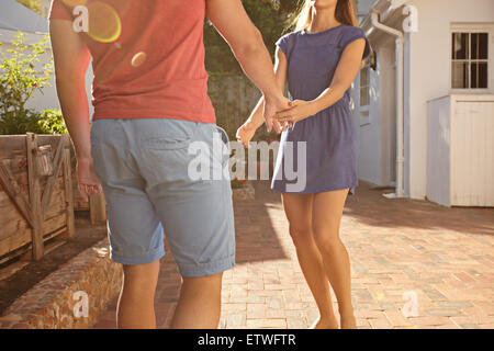 Cropped shot of young couple standing in front of their house holding hands. Man and woman in casuals outside their - Stock Photo