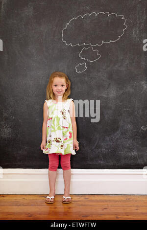 Sweet little schoolgirl with a thought bubble on blackboard looking at camera. Full length shot of caucasian young - Stock Photo