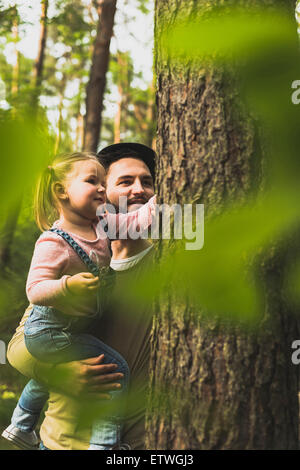 Girl with father in forest examining tree trunk - Stock Photo