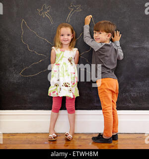 Full length portrait of cute little girl standing and little boy drawing angel wings around her on blackboard. Two - Stock Photo