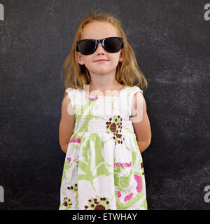 Portrait of beautiful little girl wearing sunglasses posing at camera against a black wall. - Stock Photo