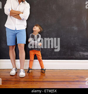 Indoor shot of little boy and his father standing with hands folded against black wall. Father and son looking at - Stock Photo