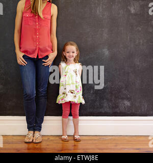 Indoor shot of beautiful little girl standing with her mother smiling. Mother and daughter posing against a black - Stock Photo