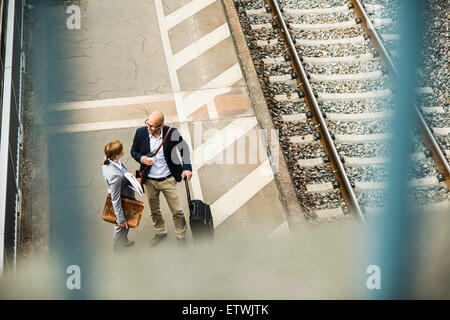 Businessman and businesswoman talking on railway platform - Stock Photo