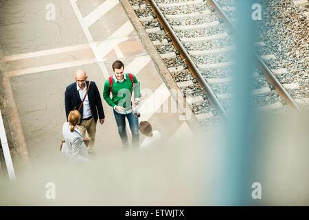 Businesspeople talking on railway platform - Stock Photo