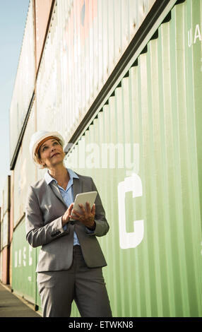 Businesswoman with digital tablet wearing safety helmet at container port - Stock Photo