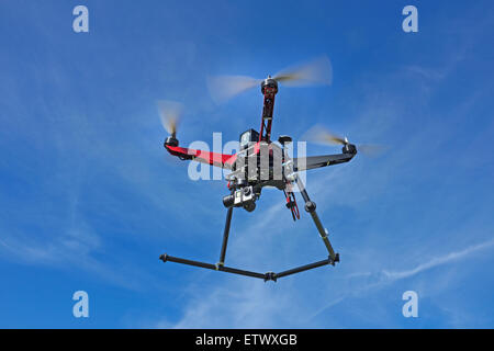A quadcopter drone, equipped with a gopro camera, in flight. - Stock Photo