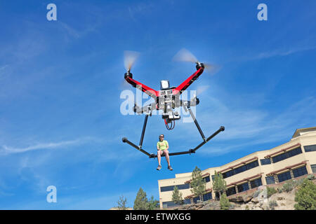 A person being delivered by a quadcopter drone, equipped with a gopro camera, in flight. - Stock Photo