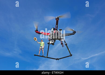 Same day delivery via a quadcopter drone, equipped with a gopro camera, in flight. - Stock Photo