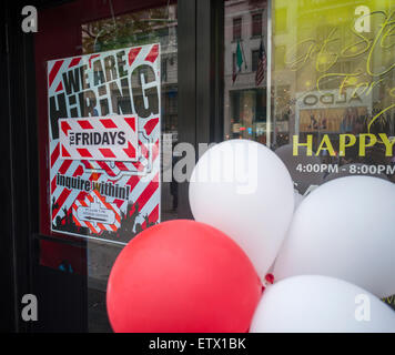 A sign in the window of a T.G.I. Friday's casual dining restaurant in New York informs that the chain is hiring, - Stock Photo