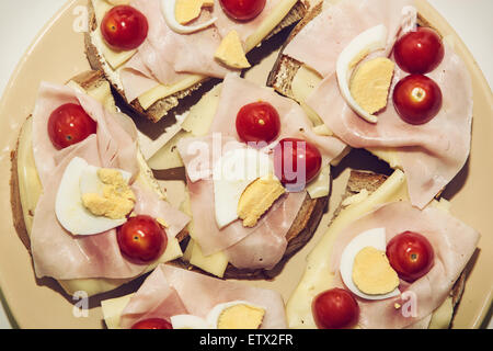 Tasty sandwiches with egg, cheese, ham and cherry tomatoes. Food and drink theme. - Stock Photo