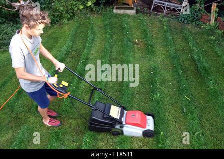 Berlin, Germany, boy mows the lawn in a garden - Stock Photo