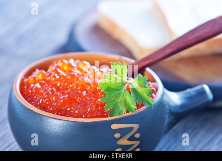red salmon caviar in bowl and on a table - Stock Photo