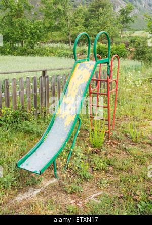 Children`s slide in overgrown playground in rural village in Spain - Stock Photo