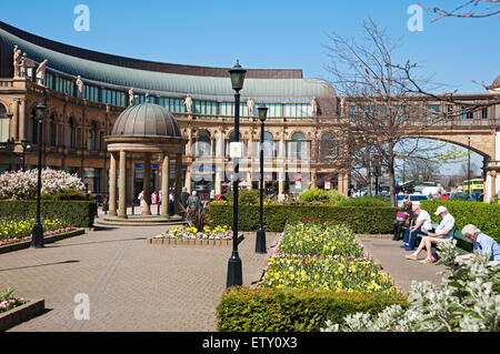 People relaxing in Victoria Gardens in spring and Victoria Shopping Centre Harrogate North Yorkshire England UK - Stock Photo