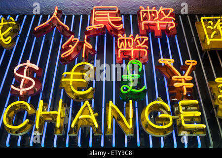 Neon lights listing various currencies above currency exchange shop at night in Hong Kong China - Stock Photo