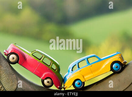 2 dinky Austin Devon's in contrasting bright colors, resting on a boot in rolling Devonshire countryside - Stock Photo