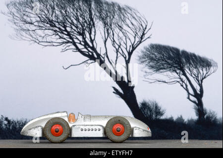 dinky racing car, called 'Speed of the wind' set against wind swept trees. - Stock Photo