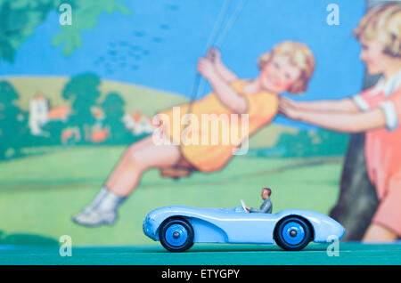 dinky sports car driving through countryside in summer against a painted back ground of children on a swing. - Stock Photo
