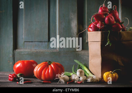 Heap of fresh ripe colorful vegetables tomatoes, chili peppers, green onion and bunch of radish in paper bag over - Stock Photo
