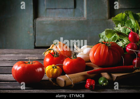 Heap of fresh ripe colorful vegetables tomatoes, chili peppers, green onion and bunch of radish on wooden chopping - Stock Photo