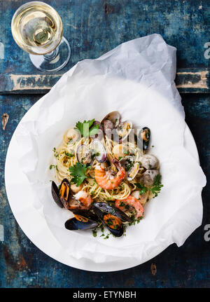 Seafood pasta and wine - Spaghetti with clams, prawns, sea scallops on blue background