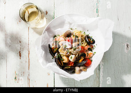 Seafood pasta and wine - Spaghetti with clams, prawns, sea scallops on white plate
