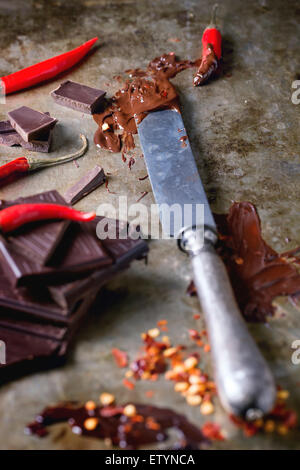Chopping and melting dark chocolate with fresh and dry red hot chili peppers and vintage knife over old metal background. - Stock Photo