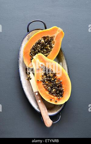 Sliced fresh papaya fruit on an enamel plate - Stock Photo