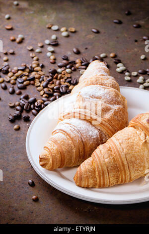 Plate with two fresh baked croissants with heap od roasted and  unroasted coffee beans over rusty metal background. - Stock Photo