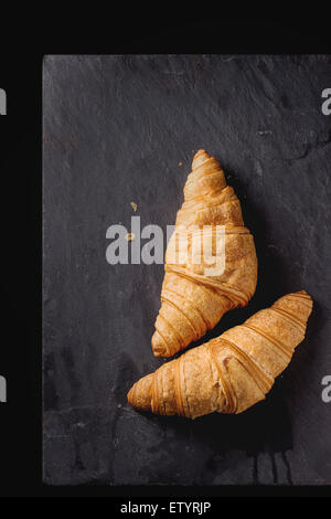 Two fresh baked croissants on black slate. Top view. - Stock Photo