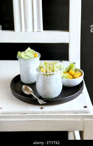 Kiwi ,mango and chia seeds pudding in jar for breakfast - Stock Photo